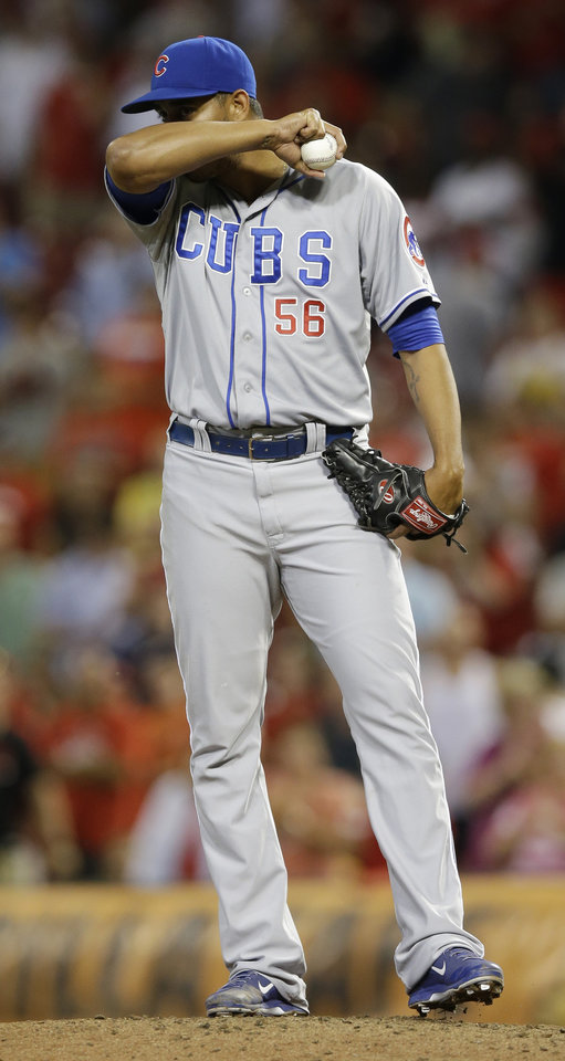Photo - Chicago Cubs relief pitcher Hector Rondon wipes his face in the ninth inning of a baseball game against the Cincinnati Reds, Tuesday, July 8, 2014, in Cincinnati. Rondon was the losing pitcher in the game won by Cincinnati 6-5. (AP Photo/Al Behrman)