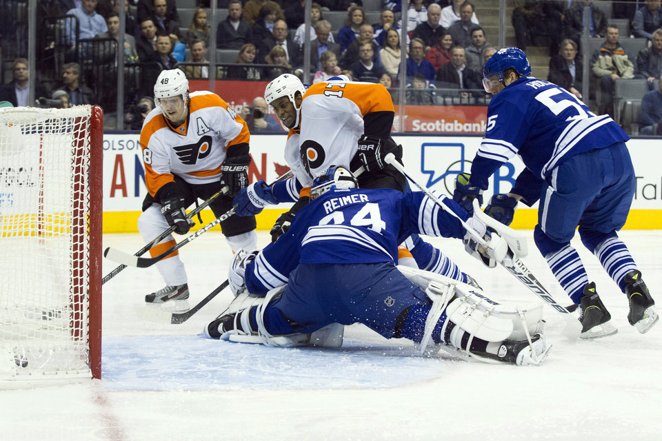 Philadelphia Flyers\' Wayne Simmonds, center, scores on Toronto Maple Leafs goaltender James Reimer as Flyers\' Danny Briere, left, and Leafs\' Korbinian Holzer watch during the first period of their NHL hockey game, Monday, Feb. 11, 2013, in Toronto. (AP Photo/The Canadian Press, Chris Young)