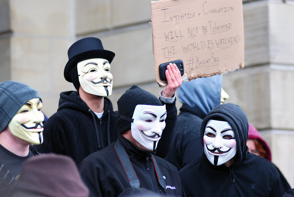 Photo - In this Dec. 29, 2012 photo, members of the group Anonymous, wearing Guy Fawkes masks and other decorative attire, protest in front of the Jefferson County Courthouse in Steubenville, Ohio.  Hacker-activists associating under the Anonymous and KnightSec labels allege a cover-up or contend more people should be charged in the case of two eastern Ohio high school football players charged with raping a 16-year-old girl. (AP Photo/Herald-Star, Michael D. McElwain)