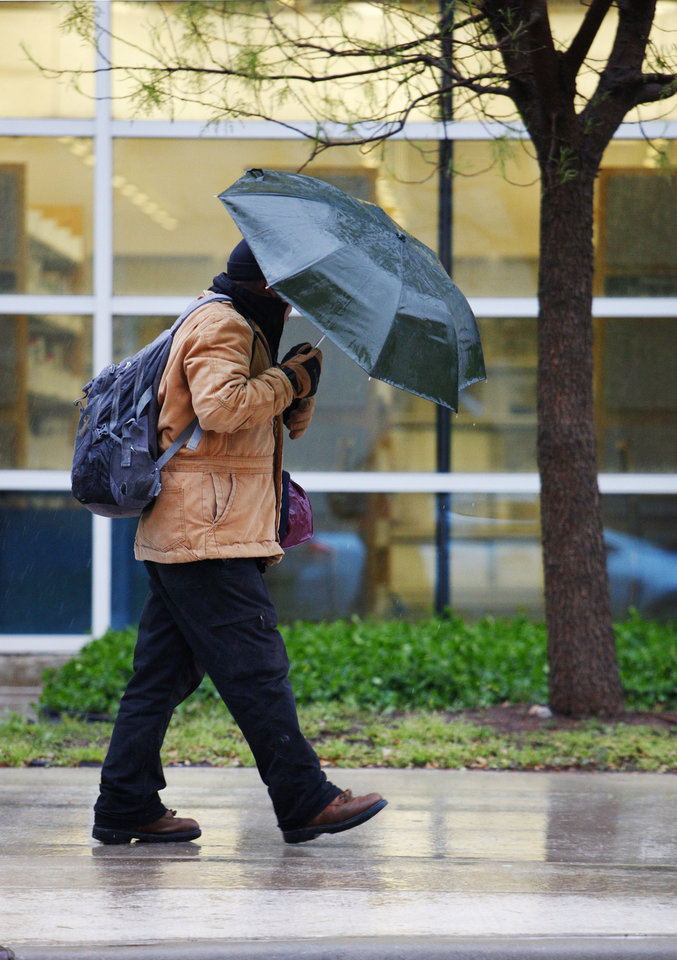 Photo - A pedestrian walking in the rain with an umbrella past the Ronald J. Norick Downtown Library on Park Avenue in Oklahoma City Wednesday, April 10, 2013. Photo by Paul B. Southerland, The Oklahoman