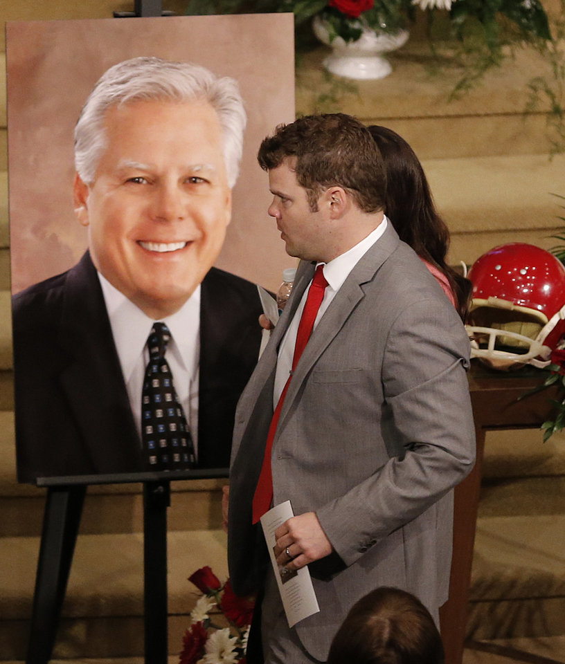 Photo - Bo Davis walks by a photo of his father Steve during the funeral for his dad and former University of Oklahoma football player Steve Davis at the First Baptist Church on Monday, March 25, 2013, in Tulsa, Okla. Davis died in a plane crash last week in Indiana. Photo by Chris Landsberger, The Oklahoman