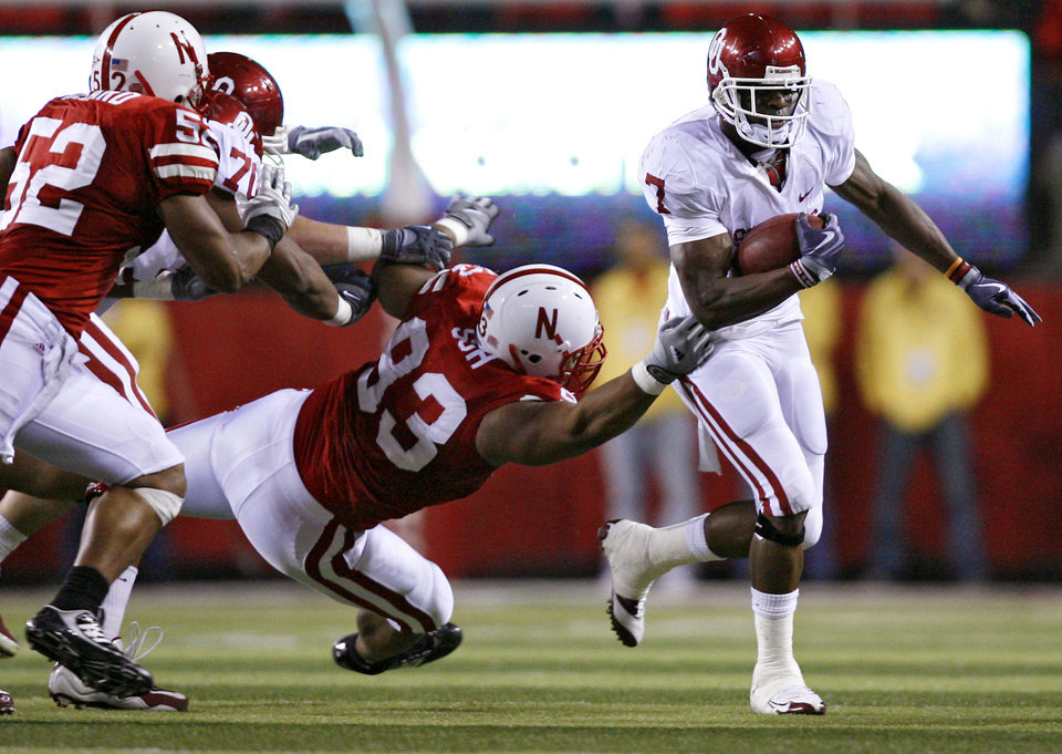 Photo - Oklahoma's DeMarco Murray (7) gets past Nebraska's Ndamukong Suh (93) during the first half of the college football game between the University of Oklahoma Sooners (OU) and the University of Nebraska Cornhuskers (NU) on Saturday, Nov. 7, 2009, in Lincoln, Neb.