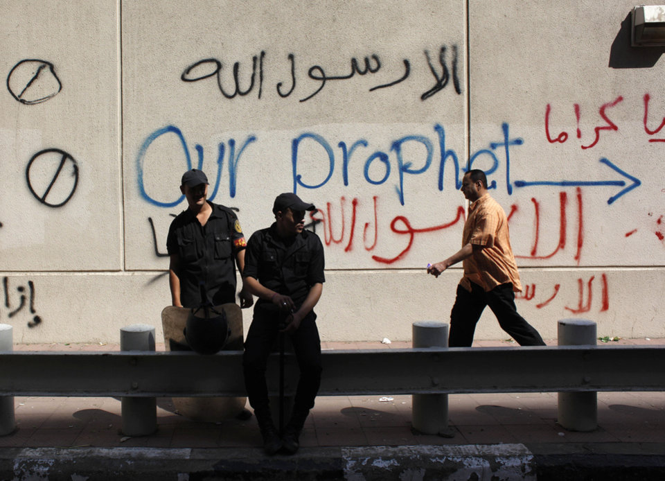 Photo -   CORRECTS NATIONALITY OF FILMMAKER - Egyptian soldiers stand guard in front of the U.S. embassy in Cairo, Egypt, Wednesday, Sept. 12, 2012, as part of widespread anger across the Muslim world about a film ridiculing Islam's Prophet Muhammad. A man identifying himself as Sam Bacile, a 56-year-old California real estate developer, said he wrote, produced and directed the movie. He told the AP he was an Israeli Jew and an American citizen. But Israeli officials said they had not heard of Bacile and there was no record of him being a citizen. Arabic on the wall reads,