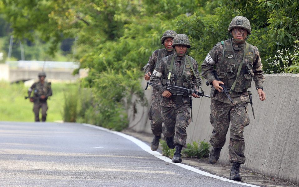 Photo - South Korean army soldiers run during an arrest operation in Goseong, South Korea, Monday, June 23, 2014. The parents of a runaway South Korean soldier suspected of killing five comrades at an outpost near the tense border with North Korea pleaded with him to surrender Monday as the military were besieging him and trying to capture him alive, officials said.(AP Photo/Yonhap, Hwang Kwang-mo)  KOREA OUT