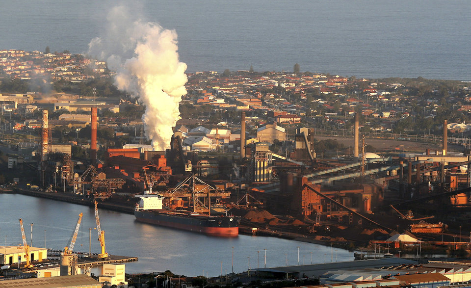 Photo - In this July 2, 2014 photo, smoke billows out of a chiming chimney stack of steel works factories in Port Kembla 86 kilometers (53 miles) south of Sydney. The Senate is expected to vote as early as Monday, July 7, 2014, to repeal an unpopular, two-year-old tax charged to around 300 of the country's biggest carbon polluters. (AP Photo/Rob Griffith)