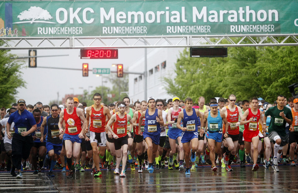 Photo - Runners sprint off the starting line of the 14th Annual Oklahoma City Memorial Marathon in Oklahoma City, Sunday, April 27, 2014. The marathon was delayed over two hours beyond it's original start time of 6 a.m. Photo by KT King/The Oklahoman