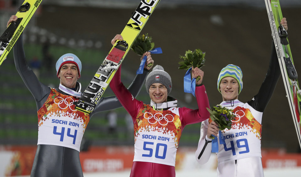 Photo - Poland's gold medal winner Kamil Stoch is flanked by Norway's bronze medal winner Anders Bardal, left, and Slovenia's silver medal winner Peter Prevc after the the men's normal hill ski jumping final at the 2014 Winter Olympics, Sunday, Feb. 9, 2014, in Krasnaya Polyana, Russia. (AP Photo/Matthias Schrader)