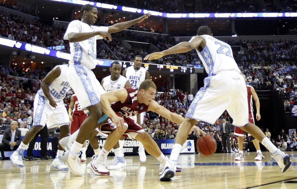 Photo - Oklahoma's Blake Griffin (23) looses the ball under the defensive pressuer of North Carolina's Ed Davis (32) and Wayne Ellington (22) during the first half in the Elite Eight game of NCAA Men's Basketball Regional between the University of North Carolina and the University of Oklahoma at the FedEx Forum on Sunday, March 29, 2009, in Memphis, Tenn.