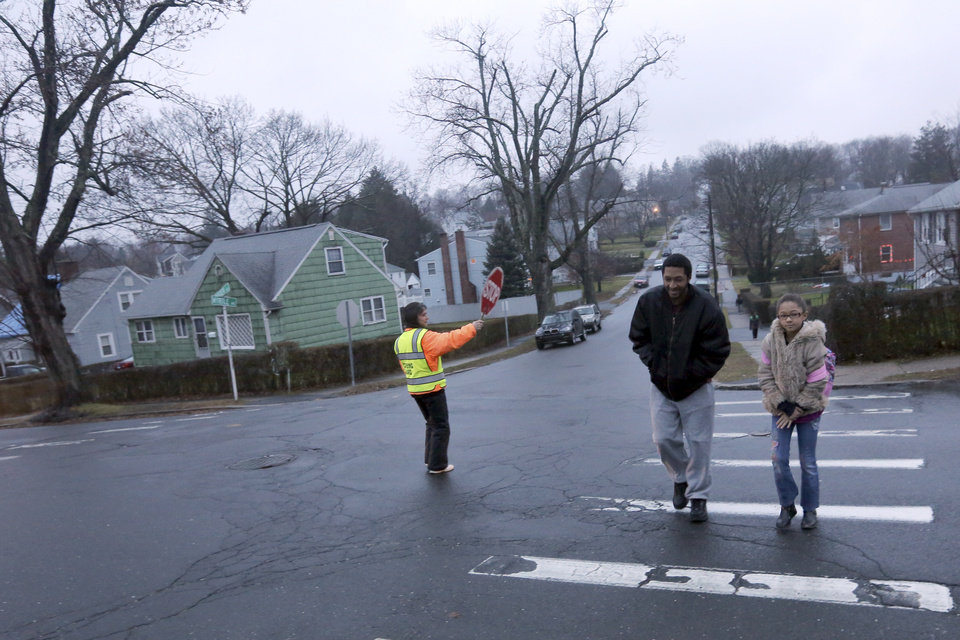 Photo - Rudy McCarley, left, walks his daughter Zarina to the Morris Street Elementary School, Monday, Dec. 17, 2012 in Danbury, Conn. Teachers and parents across the country were wrestling with how best to quell children's fears about returning to school for the first time since the killings at Sandy Hook Elementary School in Newtown, Conn. (AP Photo/Mary Altaffer)