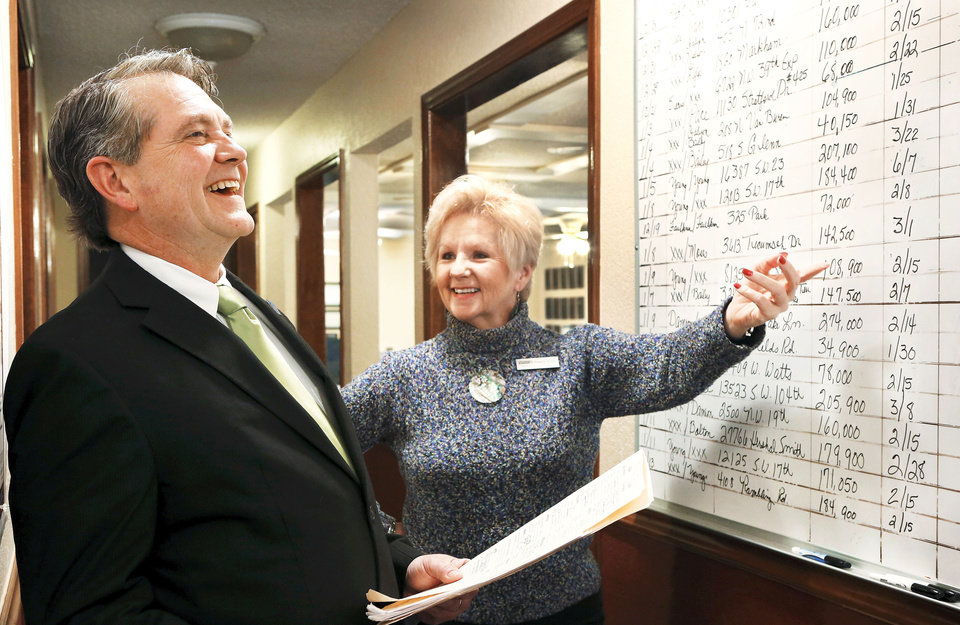 Keith Taggart, president of the Oklahoma City Metro Association of Realtors, and Realtor Paulette Statler look at a wallboard of listings at the Coldwell Banker Select office in Mustang, where Taggart is managing broker. Photo by Jim Beckel, THE OKLAHOMAN