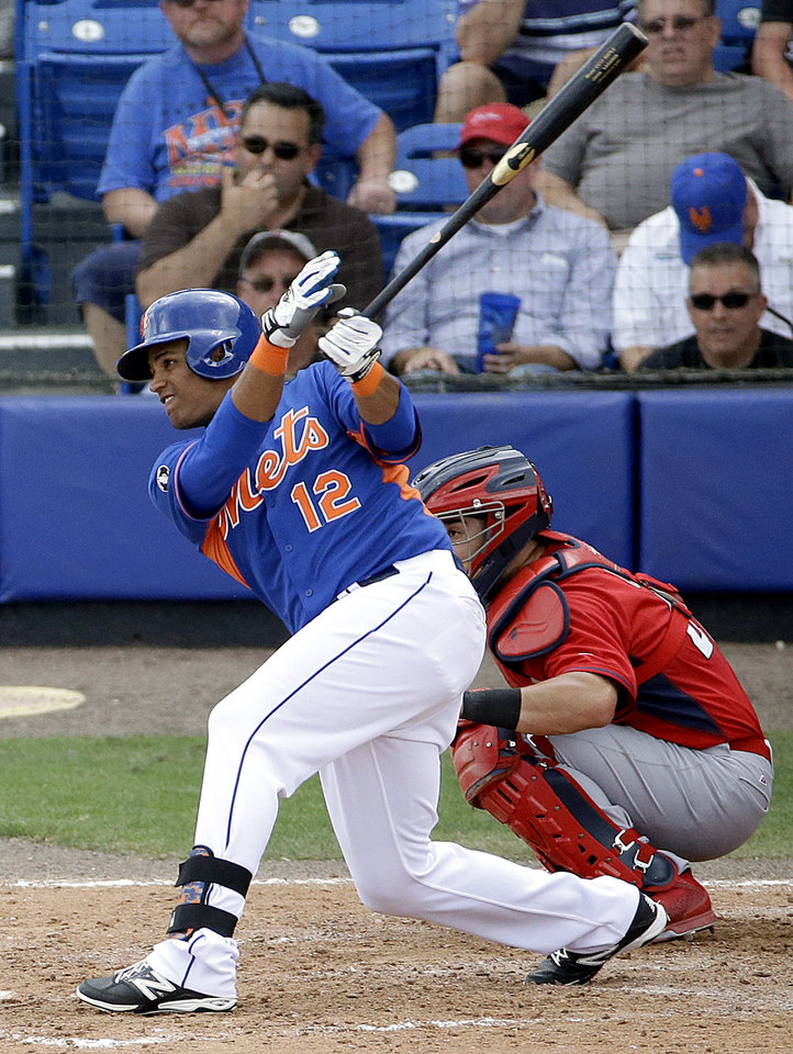 Photo - New York Mets' Juan Lagares hits a single to score teammates Eric Campbell and Andrew Brown in the seventh inning of an exhibition spring training baseball game against the St. Louis Cardinals, Wednesday, March 12, 2014, in Port St. Lucie, Fla. (AP Photo/David Goldman)