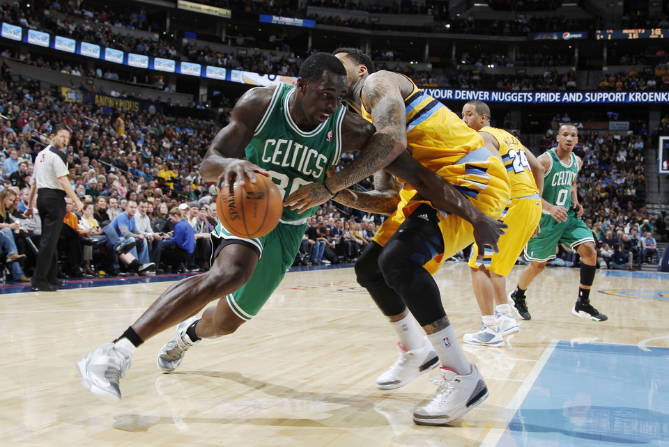 Photo - Boston Celtics forward Brandon Bass works ball inside past Denver Nuggets forward Wilson Chandler during the first quarter of an NBA basketball game in Denver on Tuesday, Feb. 19, 2013. (AP Photo/David Zalubowski)