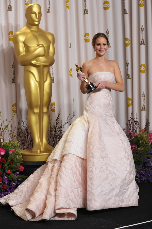 Jennifer Lawrence in Dior Haute Couture poses with her award for best actress in a leading role for