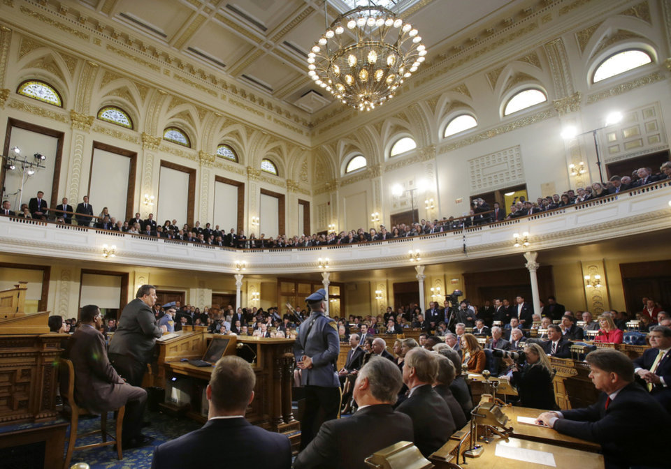 Photo - New Jersey Gov. Chris Christie, second left at podium, delivers his State Of The State address to a large crowd in the Assembly Chambers of the Statehouse, Tuesday, Jan. 8, 2013, in Trenton, N.J. Christie promised in his annual State of the State address Tuesday that New Jersey will be back