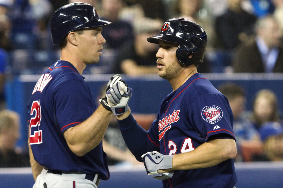 Photo -   Minnesota Twins' Trevor Plouffe, right, celebrates with Chris Parmelee after hitting a two-run, home run against the Toronto Blue Jays during the second inning of a baseball game, Monday, Oct. 1, 2012, in Toronto. (AP Photo/The Canadian Press, Chris Young)