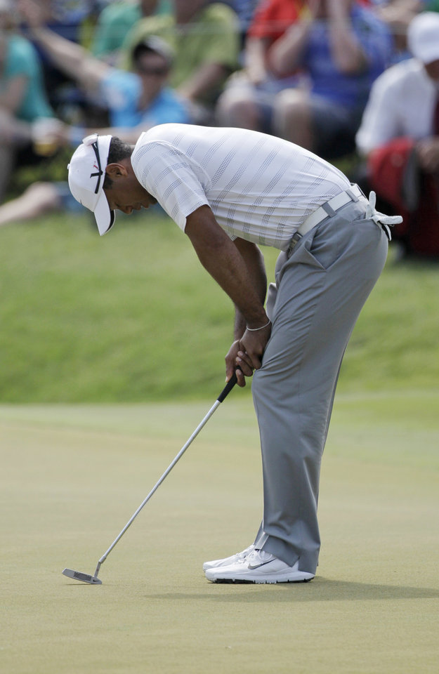 Photo -   Tiger Woods reacts to a missed birdie putt on the 18th hole during the third round of the Players Championship golf tournament at TPC Sawgrass, Saturday, May 12, 2012, in Ponte Vedra Beach, Fla. (AP Photo/David Goldman)