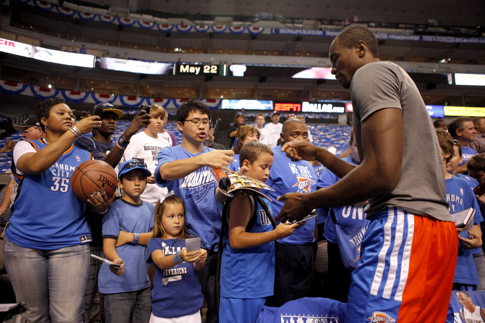 Photo - Oklahoma City's Serge Ibaka signs autographs for fans before Game 4 of the first round in the NBA playoffs between the Oklahoma City Thunder and the Dallas Mavericks at American Airlines Center in Dallas, Saturday, May 5, 2012. Photo by Bryan Terry, The Oklahoman