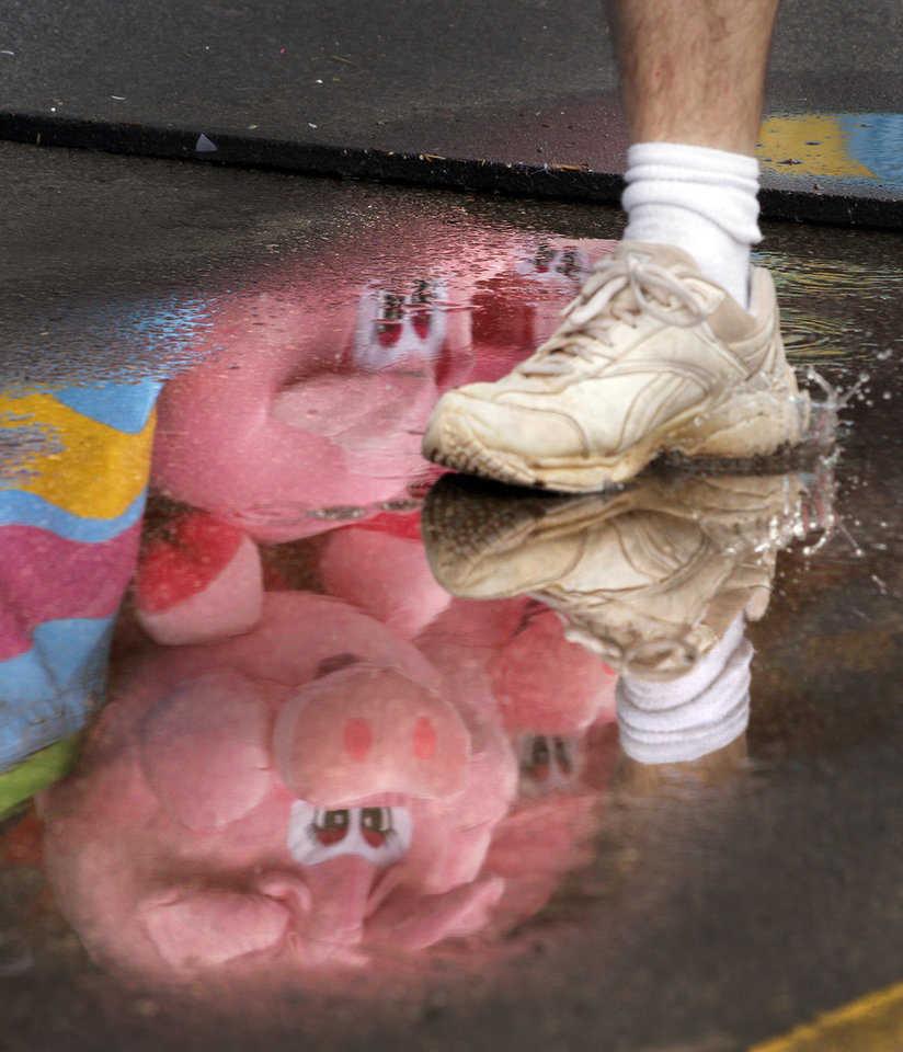 A stuffed pig is reflected in a pool of rain water on the Midway of the Oklahoma State Fair in Oklahoma City , Tuesday, September 22, 2011. Photo by Steve Gooch