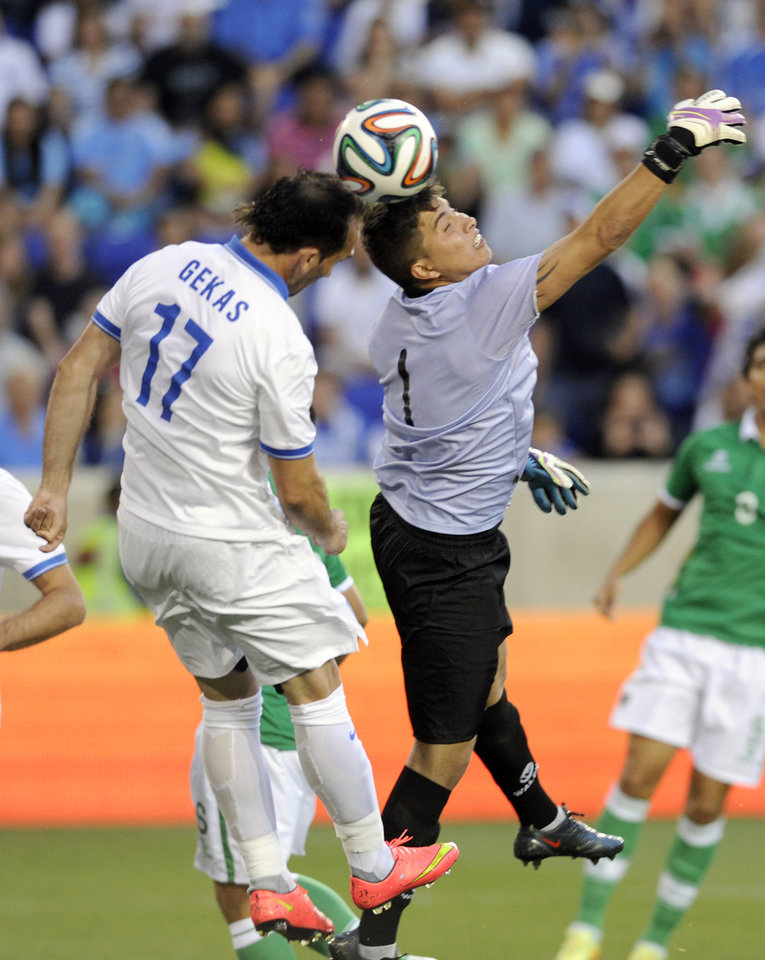 Photo - Bolivia goalkeeper Romel Javier Quinonez goes up for a save as Greece's Thoefanis Gekas attempts a header during the first half of an international friendly soccer match Friday, June 6, 2014, in Harrison, N.J.. (AP Photo/Bill Kostroun)