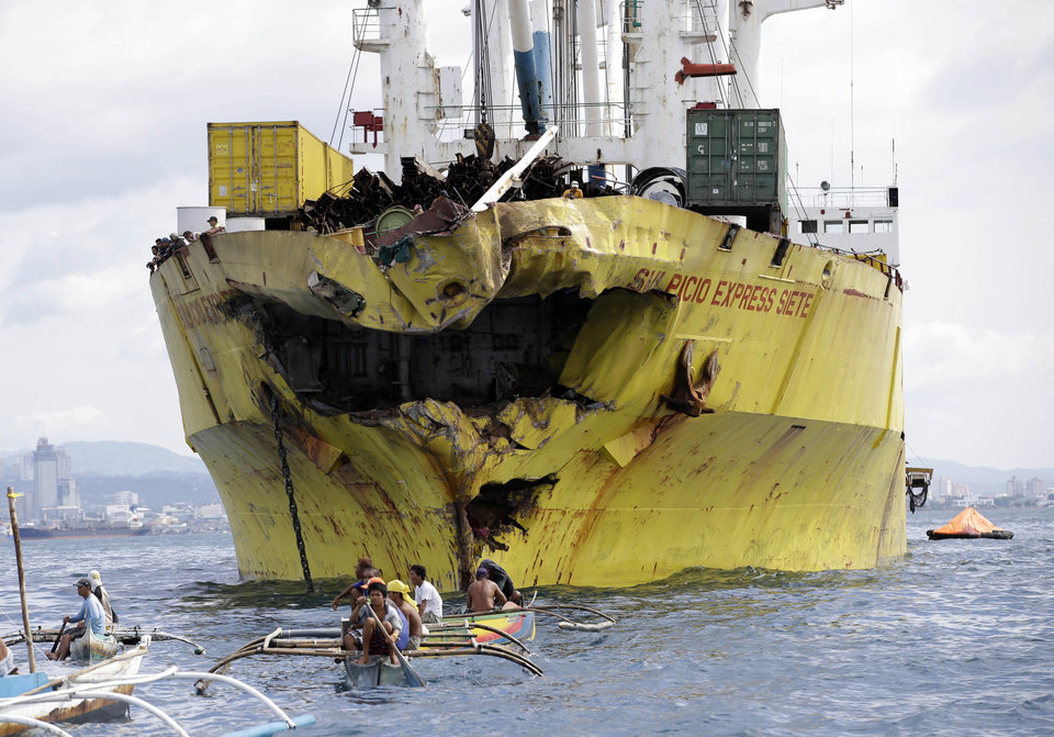 Photo - Volunteers search near the damaged cargo ship Sulpicio Express Siete a day after it collided with a passenger ferry off the waters of Talisay city, Cebu province in central Philippines, Saturday Aug. 17, 2013. Divers combed through a sunken ferry Saturday to retrieve the bodies of more than 200 people still missing from an overnight collision with a cargo vessel near the central Philippine port of Cebu that sent passengers jumping into the ocean and leaving many others trapped. At least 28 were confirmed dead and hundreds rescued. The captain of the ferry MV Thomas Aquinas, which was approaching the port late Friday, ordered the ship abandoned when it began listing and then sank just minutes after collision with the MV Sulpicio Express, coast guard deputy chief Rear Adm. Luis Tuason said. (AP Photo/Bullit Marquez)