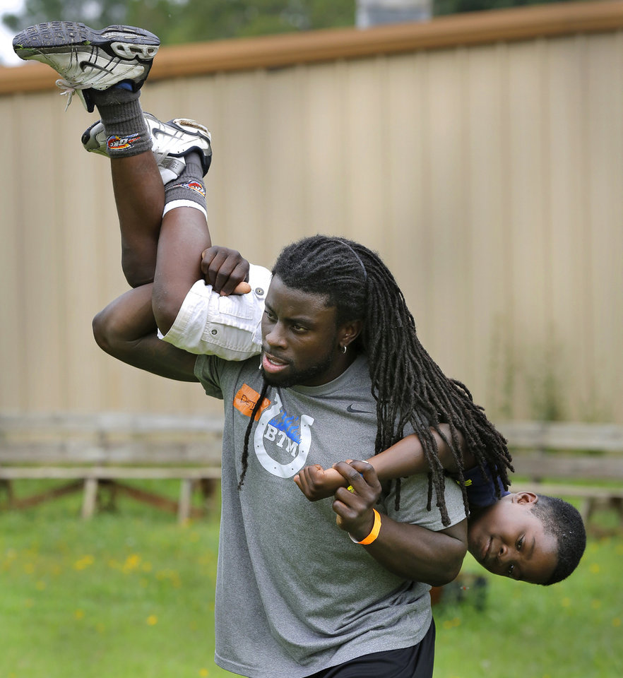 Photo -  Deji Karim carries a boy on his shoulders to the next event station. Photo by Jim Beckel, The Oklahoman   Jim Beckel -  THE OKLAHOMAN