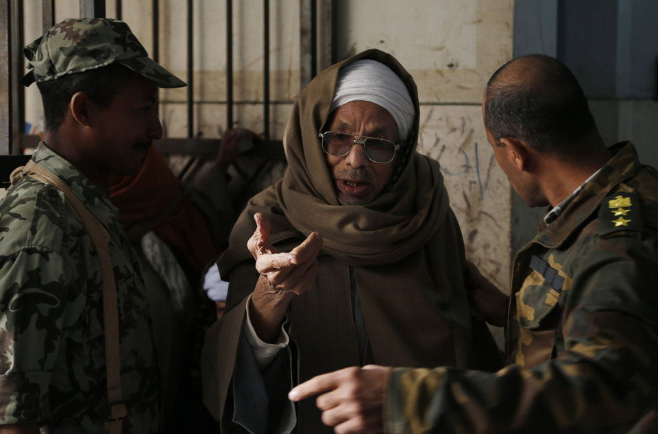 An Egyptian man speaks with soldiers before casting his vote during a referendum on a disputed constitution drafted by Islamist supporters of President Mohammed Morsi in Cairo, Egypt, Saturday, Dec. 15, 2012. Egyptians were voting on Saturday on a proposed constitution that has polarized their nation, with Morsi and his Islamist supporters backing the charter, while liberals, moderate Muslims and Christians oppose it. (AP Photo/Petr David Josek)