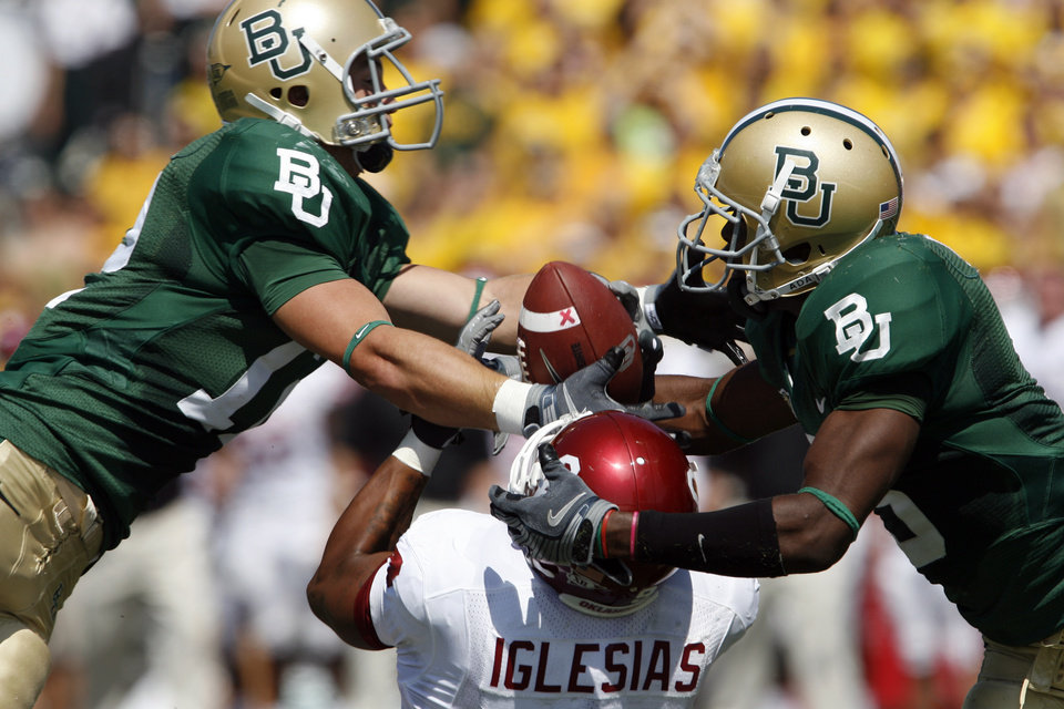 Jake La Mar (12 left) and Antareis Bryan (3, right) fight for a pass with Juaguin Iglesiasin the first half during the college football game between Oklahoma (OU) and Baylor University at Floyd Casey Stadium in Waco, Texas, Saturday, October 4, 2008.  The play was reviewed and determined that the ball never hit the ground and Baylor intercepted.  BY STEVE SISNEY, THE OKLAHOMAN