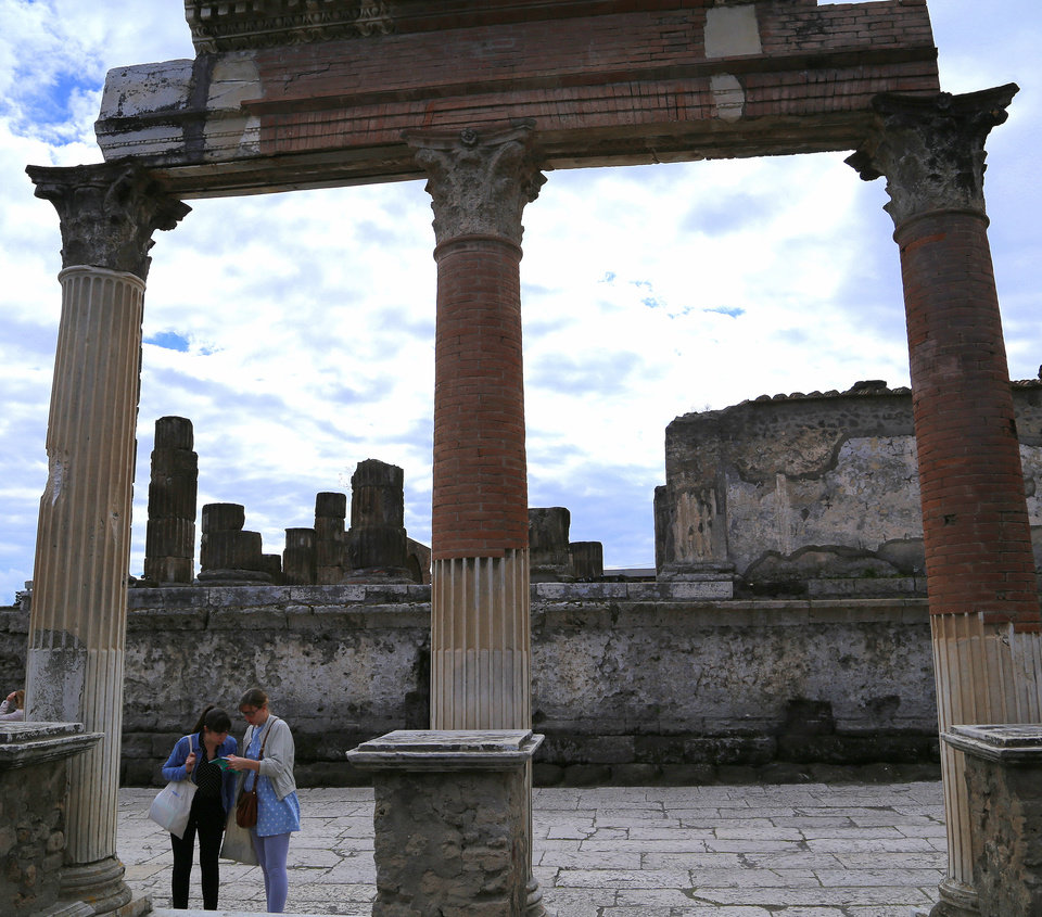 Photo - In this May 14, 2014 photo, partially restored columns stand in the old forum of Pompeii, an ancient town near modern-day Naples, Italy, that was destroyed in A.D. 79 following the eruption of Mount Vesuvius. An estimated 2.5 million people visit the ruins each year.  (AP Photo/Michelle Locke)