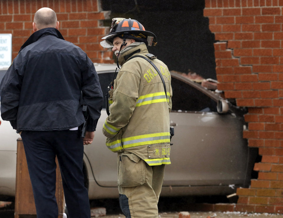 An Oklahoma City firefighter and a police officer  look at damage to the north wall of the Skyview Nursing Center after a car drove through the brick exterior and into a resident's room on Thursday morning, Jan. 10, 2013. A firefighter at the scene said the car was occupied by a female driver when it plowed into the building at 2200 N. Coltrane. The room was unoccupied at the time of the accident and officials said there were no reported injuries.    Photo by Jim Beckel, The Oklahoman
