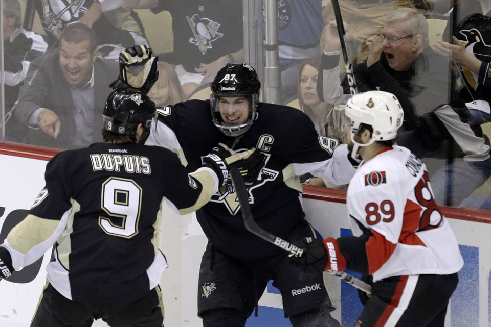 Photo - Pittsburgh Penguins' Sidney Crosby (87) celebrates scoring his second goal of the first period with teammate Pascal Dupuis (9) as Ottawa Senators' Cory Conacher (89) skates back to his bench during Game 2 of an NHL hockey Stanley Cup second-round playoff series, in Pittsburgh on Friday, May 17, 2013.(AP Photo/Gene J. Puskar)
