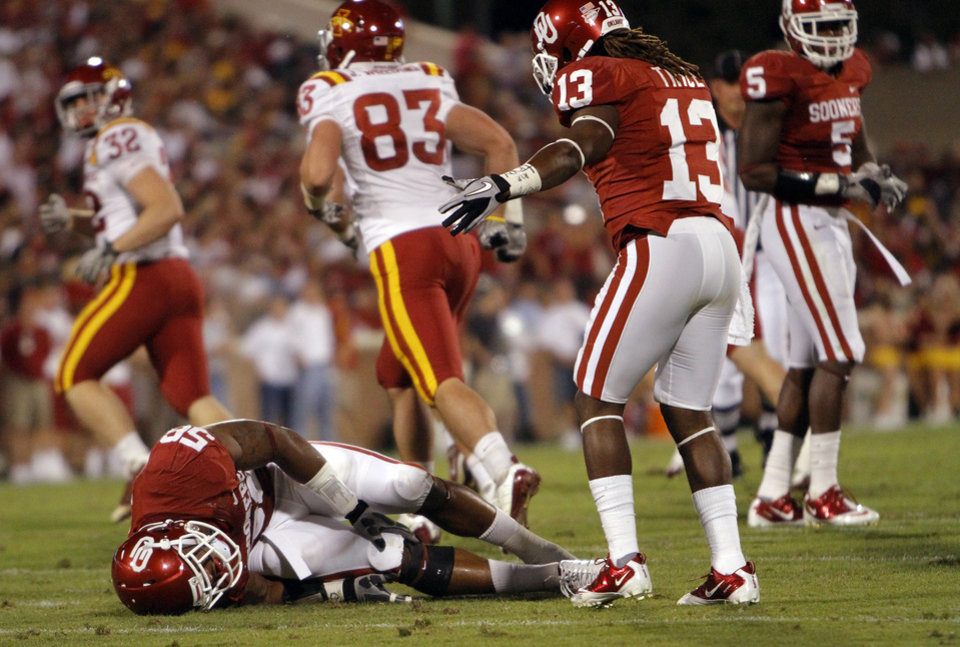 Photo - Oklahoma's Ronnell Lewis (55) grabs his knee as he lies on the ground after being injured on kick coverage during the first half of the college football game between the University of Oklahoma Sooners (OU) and the Iowa State Cyclones (ISU) at the Glaylord Family-Oklahoma Memorial Stadium on Saturday, Oct. 16, 2010, in Norman, Okla.  Photo by Chris Landsberger, The Oklahoman