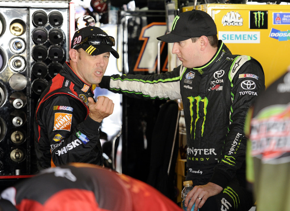 Photo - Matt Kenseth, left, talks with Kyle Busch, right, after practice for Sunday's NASCAR Sprint Cup series auto race, Saturday, Sept. 28, 2013, at Dover International Speedway in Dover, Del. (AP Photo/Nick Wass)