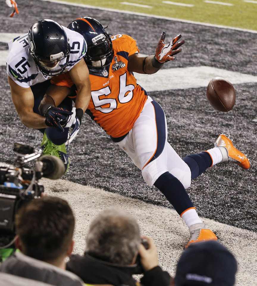 Photo - Denver Broncos outside linebacker Nate Irving (56) breaks up a pass in the end zone intended for Seattle Seahawks wide receiver Jermaine Kearse (15) during the first half of the NFL Super Bowl XLVIII football game Sunday, Feb. 2, 2014, in East Rutherford, N.J. (AP Photo/Kathy Willens)