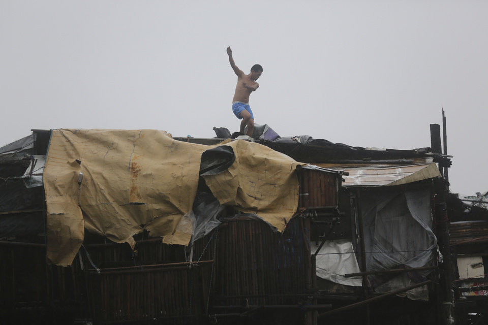 Photo - A man is thrown off balance as strong winds caused by Typhoon Koppu blow while he tries to reinforce the roof of his house at the coastal town of Navotas, north of Manila, Philippines Sunday, Oct. 18, 2015. The slow-moving typhoon blew ashore with fierce wind in the northeastern Philippines early Sunday, toppling trees and knocking out power and communications. Officials said there were no immediate reports of casualties. (AP Photo/Aaron Favila)