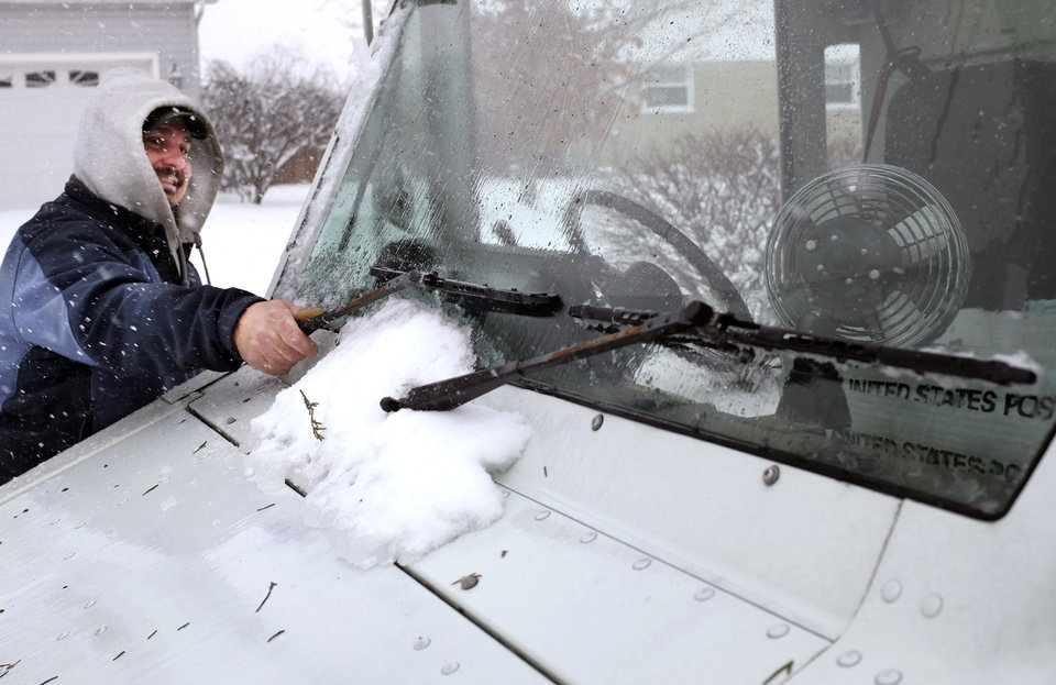 Photo - Letter carrier John Zaso clears ice and snow from the wipers of his delivery van Tuesday, Jan. 21, 2014. (AP Photo/The Winchester Star, Scott Mason)