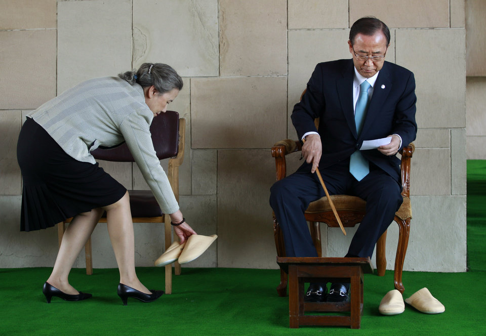 Photo -   U.N. Secretary-General Ban Ki-moon, right, reads a note as his wife Yoo Soon-taek puts a pair of slippers down after paying respects at Rajghat, the memorial to the late Mahatma Gandhi in New Delhi, India, Friday, April 27, 2012. Ban is on a three day official visit to India. (AP Photo/Kevin Frayer)