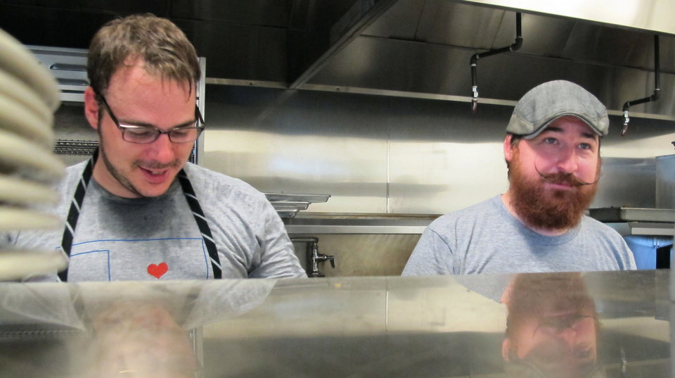 Photo - Chefs David Herny and Josh Valentine prepare to take the rush at Sunday's  portion of the OK Chefs Relief Pop-Up Restaurant in the Myriad Botanicals Gardens event space. All proceeds were donated to the Oklahoma Chapter of the American Red Cross.  DAVE CATHEY - THE OKLAHOMAN