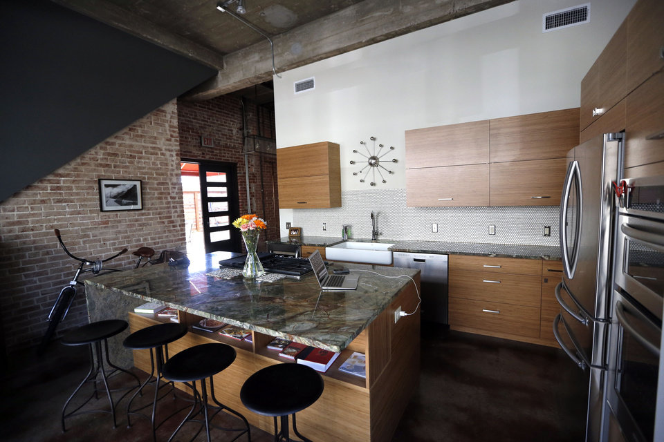 Photo - The hub of Robert Lewis's home is the kitchen and living room, essentially one space divided by a massive island-prep surface-dining counter covered with a glossy ?rain forest? granite counter top.  SARAH PHIPPS - The Oklahoman