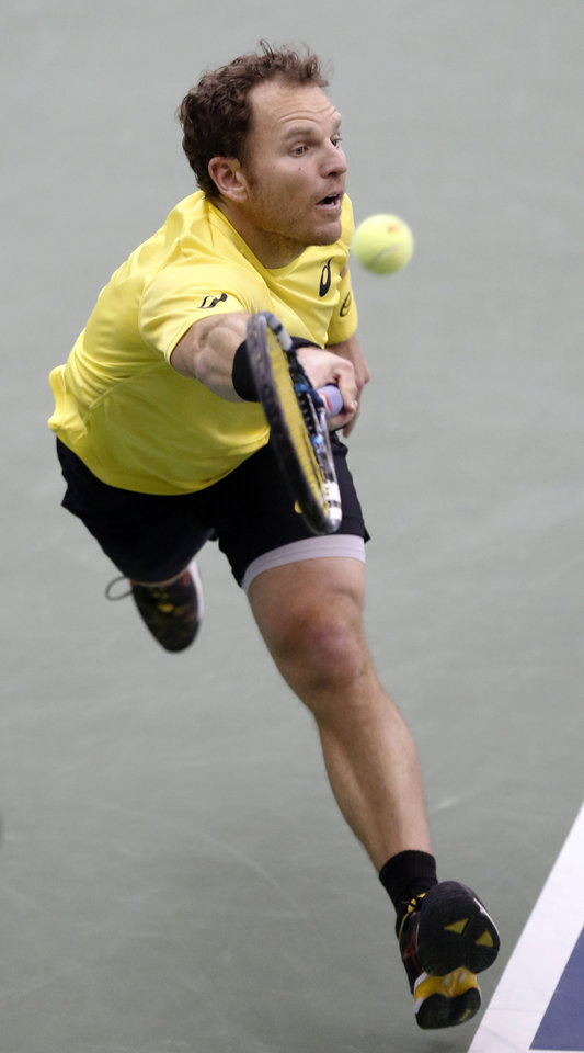 Photo - Michael Russell, of the United States, hits a return to Kei Nishikori, of Japan, in the semifinals at the U.S. National Indoor Tennis Championships on Saturday, Feb. 15, 2014, in Memphis, Tenn. Nishikori won 6-3, 6-2. (AP Photo/Rogelio V. Solis)