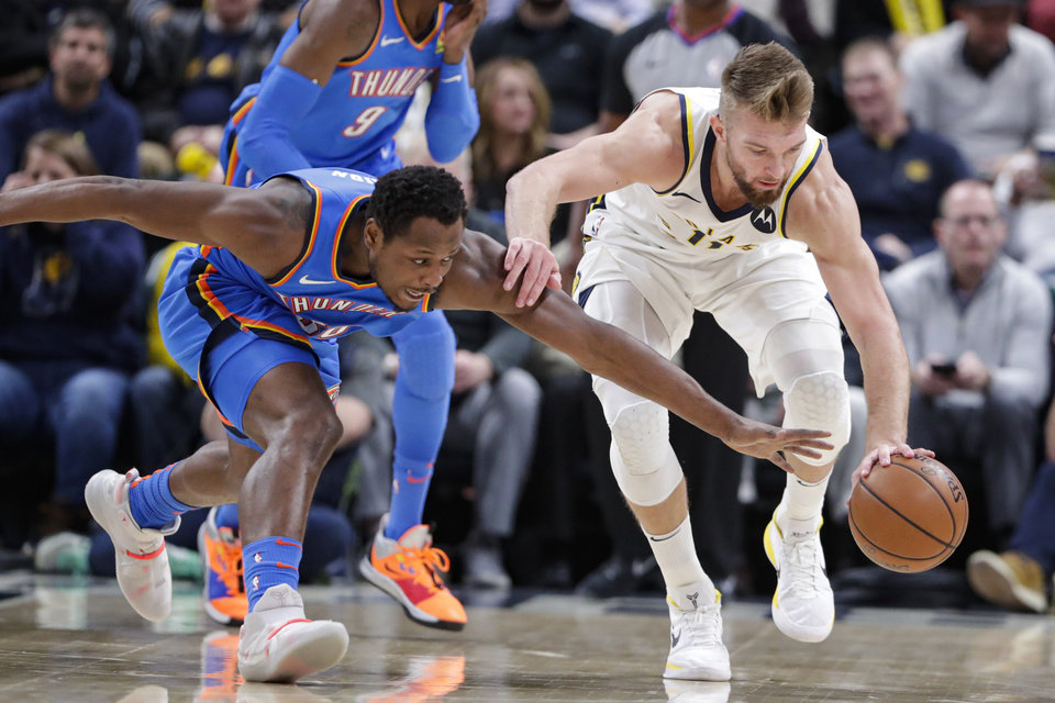 Photo - Indiana Pacers forward Domantas Sabonis (11) holds off Oklahoma City Thunder guard Deonte Burton (30) as they go for a loose ball during the second half of an NBA basketball game in Indianapolis, Tuesday, Nov. 12, 2019. The Pacers defeated the Thunder 111-85. (AP Photo/Michael Conroy)