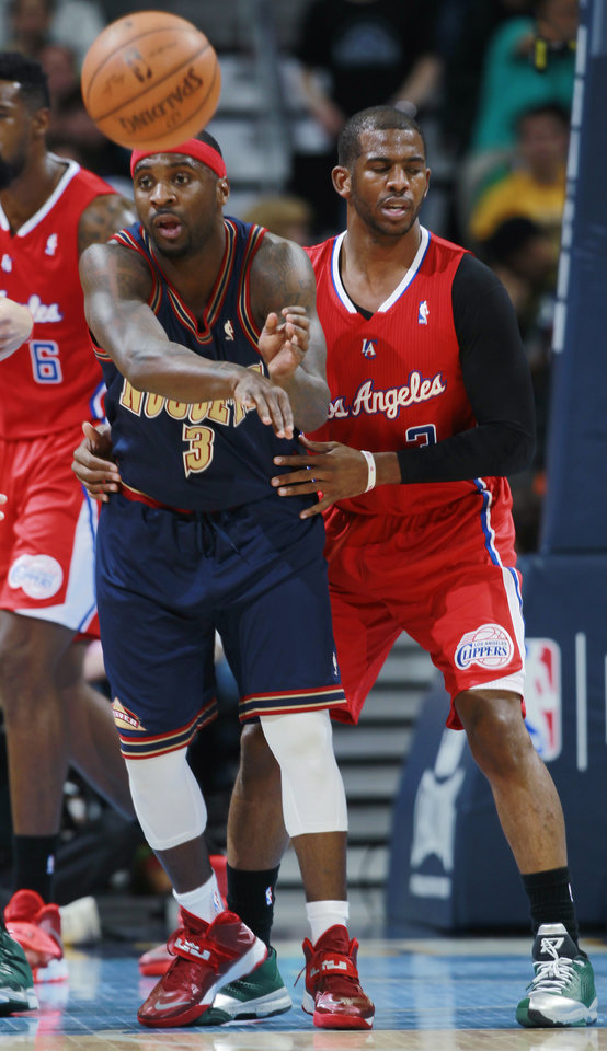 Photo - Denver Nuggets guard Ty Lawson, left, passes ball while covered by Los Angeles Clippers guard Chris Paul in the first quarter of an NBA basketball game in Denver on Monday, March 17, 2014. (AP Photo/David Zalubowski)