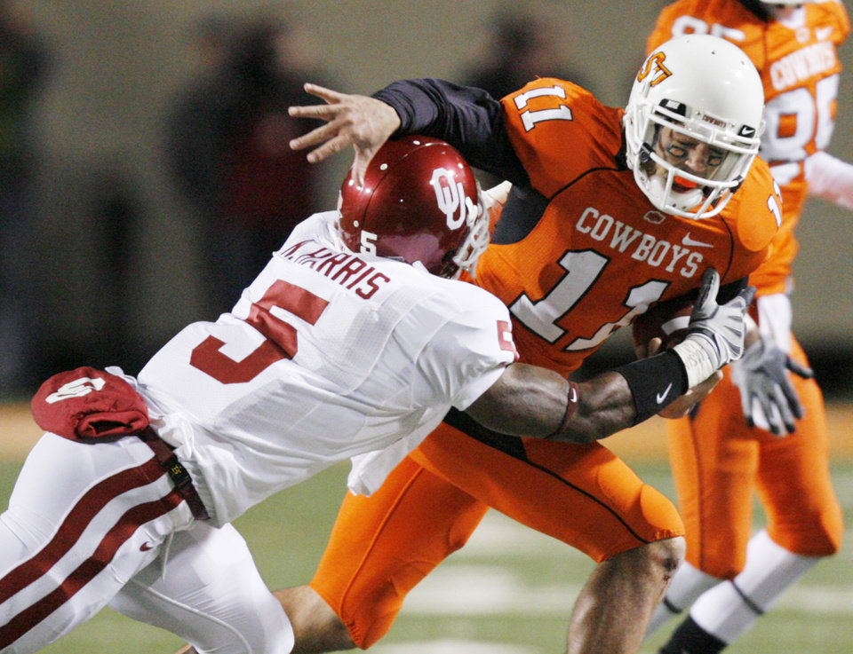 OU\'s Nic Harris brings down OSU quarterback Zac Robinson during the first half of the college football game between the University of Oklahoma Sooners (OU) and Oklahoma State University Cowboys (OSU) at Boone Pickens Stadium on Saturday, Nov. 29, 2008, in Stillwater, Okla. STAFF PHOTO BY CHRIS LANDSBERGER
