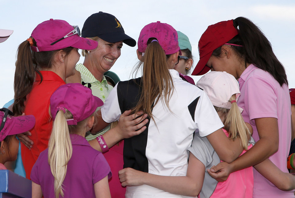 Photo - Karrie Webb, third from left, of Australia, smiles as she gets hugs from LPGA-USGA Girls Golf members, after Webb won the  LPGA Founders Cup golf tournament on Sunday, March 23, 2014, in Phoenix. (AP Photo/Ross D. Franklin)