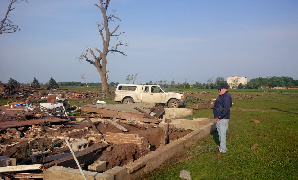 Photo - The Tuesday morning photo shows Larry Nelson, 73, surveys what's left of his home on Tuesday, June 17, 2014 in Pilger, Neb.  A storm packing rare dual tornadoes tore through the tiny farming town in northeast Nebraska on Monday.  Nelson survived the afternoon tornado by taking shelter in a neighbor's basement.  (AP Photo/Josh Funk)