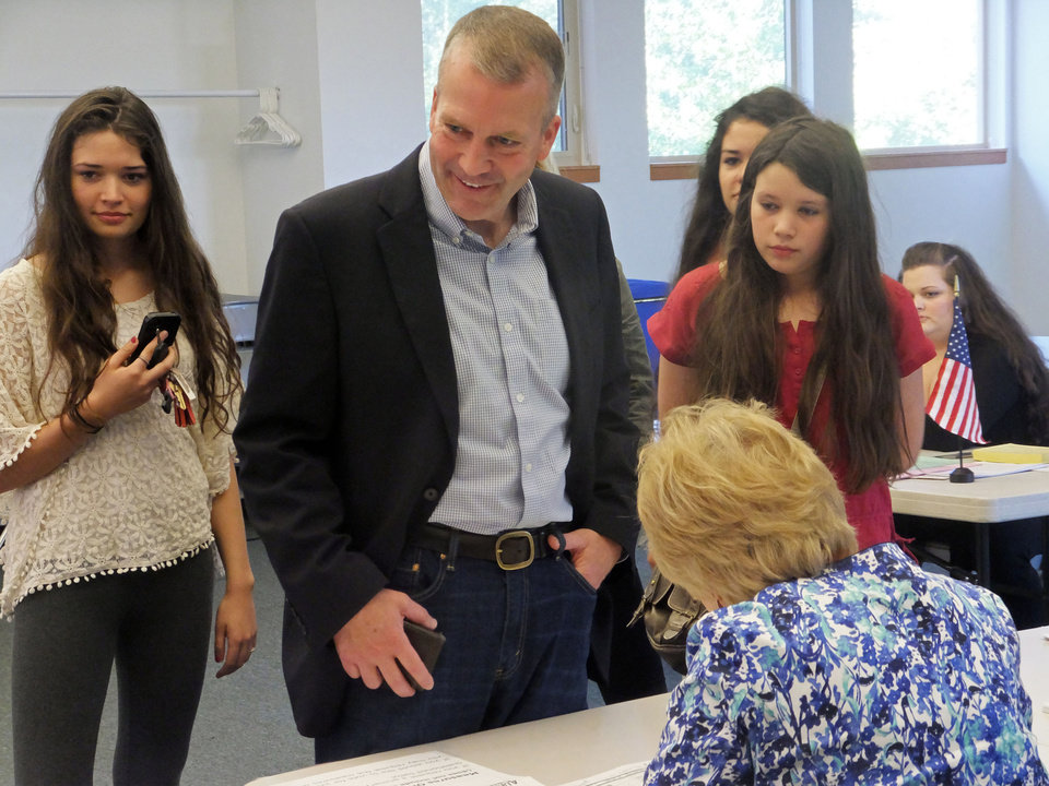Photo - Dan Sullivan, candidate for the Republican nomination for election to the U.S. Senate, signs in to cast his ballot in Alaska's primary election in Anchorage, Tuesday, Aug. 19, 2014. His daughters look on behind him. (AP Photo/Becky Bohrer)