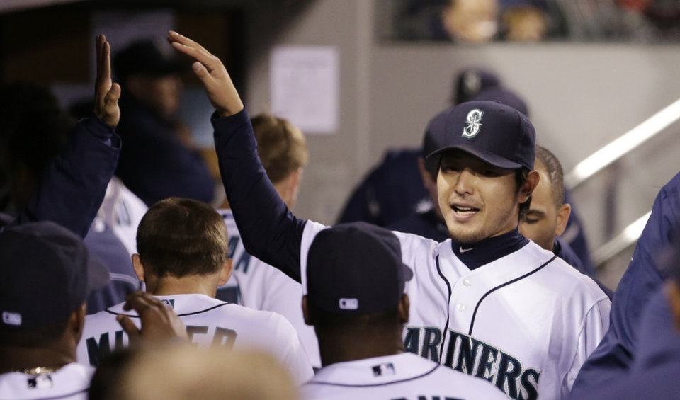 Photo - Seattle Mariners starting pitcher Hisashi Iwakuma is greeted by teammates as he leaves the baseball game in the eighth inning against the Kansas City Royals Wednesday, Sept. 25, 2013, in Seattle. (AP Photo/Elaine Thompson)
