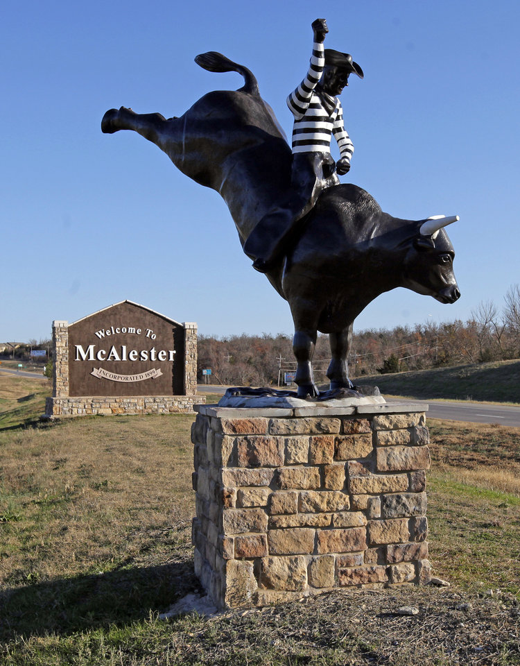 Photo - A statue of the Oklahoma State Penitentiary prison rodeo sits in front of a sign welcoming visitors to McAlester, Okla., Wednesday, Dec. 7, 2011. Photo by Nate Billings, The Oklahoman