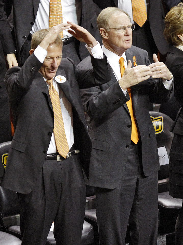 Photo - Oklahoma State athletic director Mike Holder and school president Burns Hargis jester while singing the alma mater during the memorial service for Oklahoma State head basketball coach Kurt Budke and assistant coach Miranda Serna at Gallagher-Iba Arena on Monday, Nov. 21, 2011 in Stillwater, Okla. The two were killed in a plane crash along with former state senator Olin Branstetter and his wife Paula while on a recruiting trip in central Arkansas last Thursday. Photo by Chris Landsberger, The Oklahoman