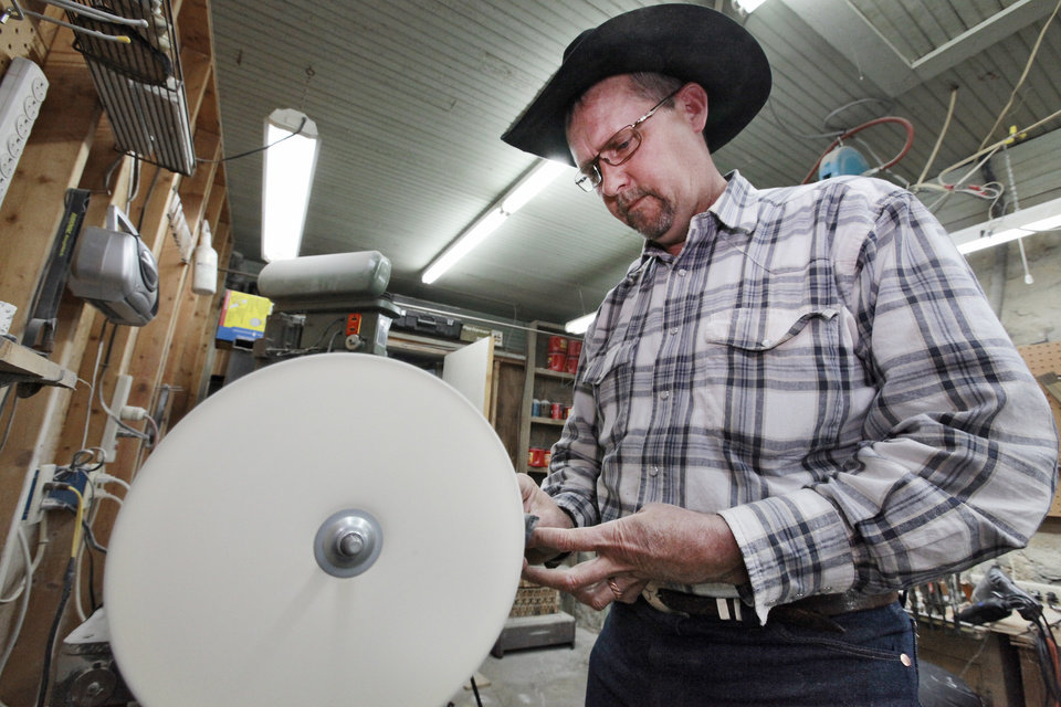 Ranch foreman James Coldren works on a  belt buckle made from cattle horns on a ranch near Foraker.  <strong>David McDaniel - The Oklahoman</strong>