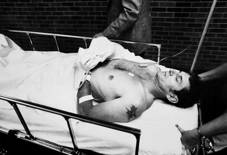 Photo - Oklahoma Highway Patrol Lt. Hoyt Hughes is brought out of a hospital emergency room after receiving treatment to his shoulder wound. Hughes was involved in a gun battle with two escapees from the Oklahoma State Penitentiary in Caddo on May 26, 1978. Three troopers were killed in the shootout, including his partner, Lt. Pat Grime.  Photo by J. Don Cook, The Oklahoman. Copy of a print from The Oklahoman Archive, Tuesday, Dec. 6, 2011.